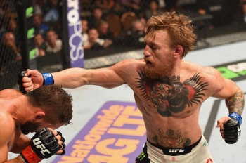 LAS VEGAS, NV - JULY 11: (R-L) Conor McGregor punches Chad Mendes in their UFC interim featherweight title fight during the UFC 189 event inside MGM Grand Garden Arena on July 11, 2015 in Las Vegas, Nevada. (Photo by Josh Hedges/Zuffa LLC/Zuffa LLC via Getty Images)